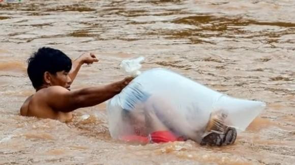 子供にきちんとした教育をうけさせたい。雨季の間、子供たちをビニール袋に入れて急流の川を渡る親たち(ベトナム)