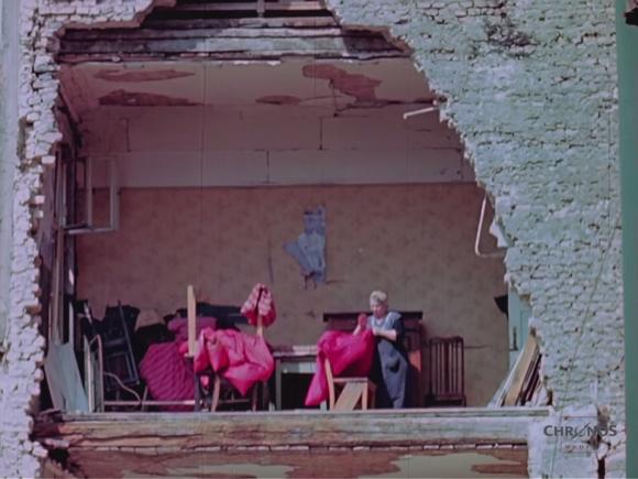 00_rs_半壊した家の中で仕事をする女性_e