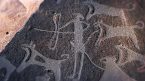 狩りをする人とリードにつながれた犬の姿。人類が描いた最古の犬の絵と思われる8000年以上前の岩面彫刻(サウジアラビア)