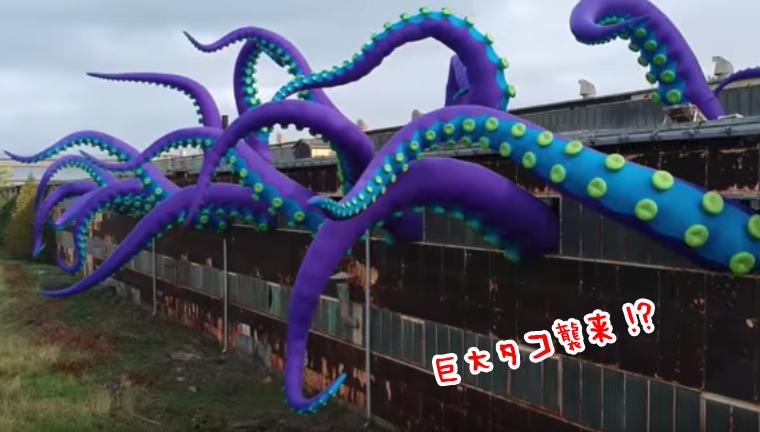 巨大タコ襲来か?廃墟風ビルから生える巨大なタコの触手。斬新なインフレータブルアート