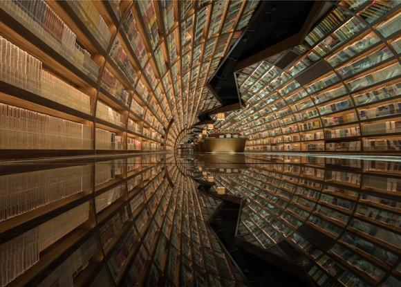 異次元につながるポータルのようだ!流線形の本棚と鏡張りの床で生み出された「書籍のトンネル」