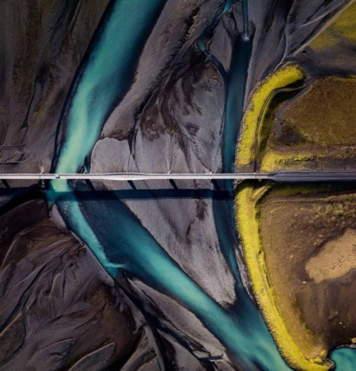 黒砂と氷河と苔を横切るアイスランドの橋