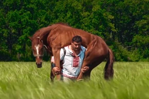 馬を背にのせユサユサ運ぶ。超人ハルク的存在感を持つ怪力男性の牧歌的光景(ウクライナ)
