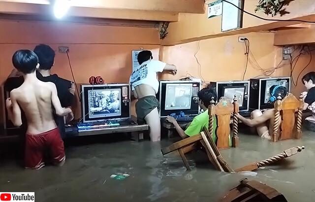 台風で洪水発生、水浸しになりながらネットカフェでゲームをプレイし続けるフィリピンの子供たち