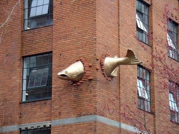 ここまで跳ねてきちゃったんかい!勢いあまってビルの壁に突き刺さった鮭のオブジェ