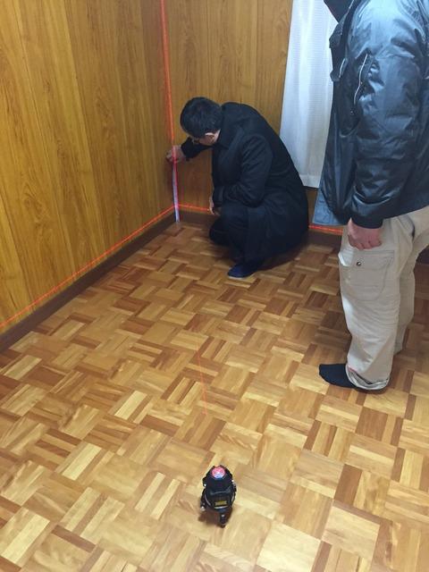 レーザー墨出し器とスケールを使って床の傾きを計測中