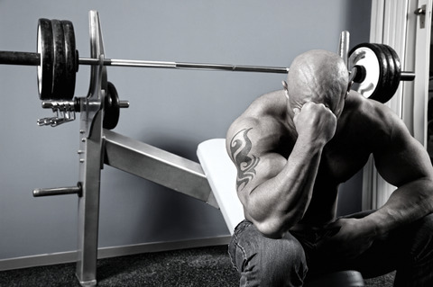 tired bodybuilder with bench press barbell