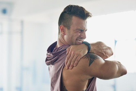 man-with-painful-shoulder-holding-it-and-grimacing