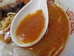 料理:激辛とんこつ赤ラーメンスープすくう@ラーメンぽんぽこ亭大橋店