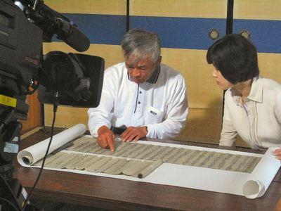 キャスターに古文書を説明する眞川さん