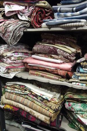 無造作に積み上げられたアンティークな布。 ハギレの他、以前カーテンやベットカバー、テーブルクロスらしき形状をして売られています。ほつれやシミなどがある場合があるのでここは慎重に品定めします。