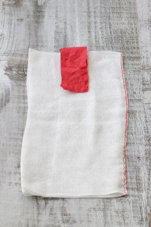 2.縫った赤い糸が右側にくるように置き、5cm×10cmの赤いペーパーをガーゼを3等分にした中央上部へ置きます。