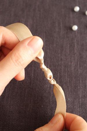 ビーズをおさえるようにさらに上を結んで留めます。 ※ビーズが落ちるのが心配なときは、透明ワイヤーにビーズを通しながら作業すると良いかも。