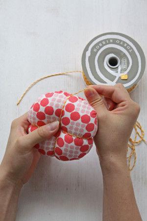 ④紐をとじ針などの太い針に通して中心から十字に 凹凸が出来るくらいきつく縛ります。 同様に十字の中間部分を十字にきつく縛ります。 これでかぼちゃピンクッションの完成です。