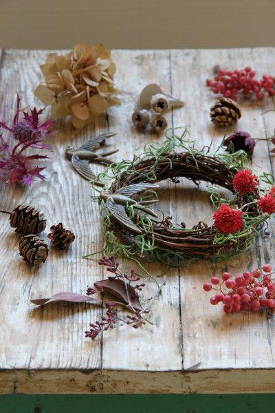 リースベースに、花材をさしてグルーガン や木工用ボンドで固定します。 木の実やドライフラワーを使うと ナチュラルなリースに。 花材で全体を覆わなくても、部分的につけて、 リースベースを見せても素敵です。