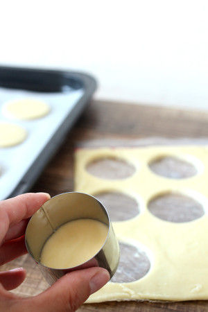 5. 冷蔵庫から袋を取り出して、 ハサミで袋の周りを切り、型で抜いて オーブンシートを敷いたトレイにのせます。 ※型がない場合は、 延べ棒みたいな形にまとめておいた生地を 5mm程の厚さに切れば 丸形のクッキーが作れます。 型で抜いてあまった生地も、 棒状にまとめて切れば無駄がありません。