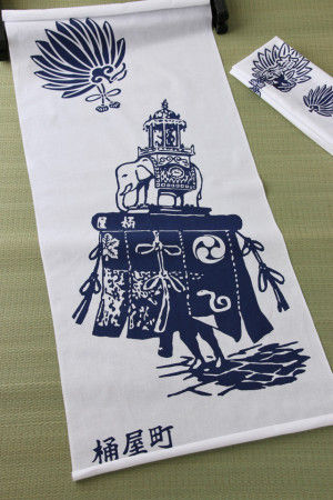 長崎くんちでは町を挙げて、 縁起ものとして町紋や町のシンボルを染め抜いた 手ぬぐいが作られます。 観客に配ったり、お祝返しにお渡ししたり、 お祭りでは、はち巻きとしても使います。