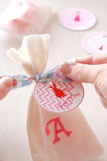 イニシャルを書き終わったら 中袋にいれたメレンゲを袋に入れて 袋の口をプリント生地でギュッと結びます。 タグをつけるときは リボンにしたプリント生地に通しておいてください。