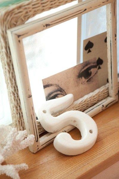 窓の前のディスプレイコーナーに飾られたアンティークの陶製ナンバープレート。モノクロのカードとともに気になるアイテムを集めて。