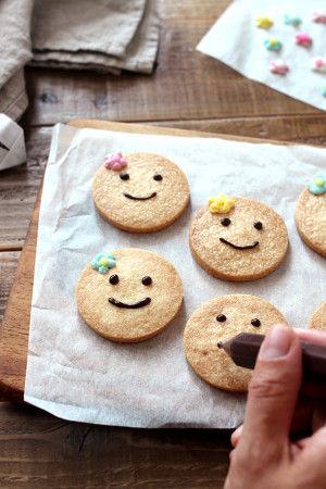 7. クッキーが焼けたら、あら熱をとって、 チョコペンでニコニコのお顔を描きます。 デコレーションをチョコペンでくっつければ完成です!