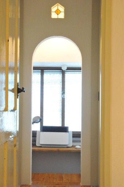 ドアを開くと、短い廊下の左右にそれぞれ収納があり、 アーチの開口部の奥は、造り付けのカウンターデスクと書棚のある 光に満たされた居心地のいい書斎になっています。