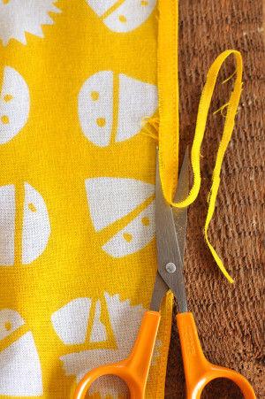 それから、先ほどの縫い目に沿って、 ハサミの刃の厚さを利用しながら、 縫い目の際をチョキチョキ切ります。
