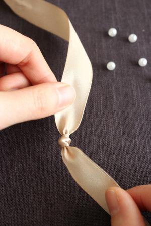 リボンの半分あたりのところに、結び目を1つ作ります。そこを中心に作っていくと左右均等になり、お好みの長を作りやすいです。