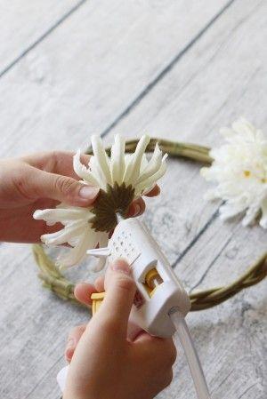 4. 「虫コナーズ」の四隅を リースにワイヤーで留めて、 お花をグルーで貼りつけていきます。