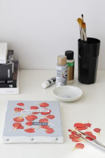 画材屋さんで売っている無地のキャンバスを アクリル絵の具でペイントし その上にカーネーションの押し花をランダムにならべ、 木工用ボンドで貼ります。 記念日やメッセージなども、 パソコンで作ってプリントしたり、 シールを貼っても。