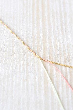 刺しゅう糸とチェーンを三つ編みします。 端をテープでとめて テーブルなどに固定すると 編みやすいですよ。