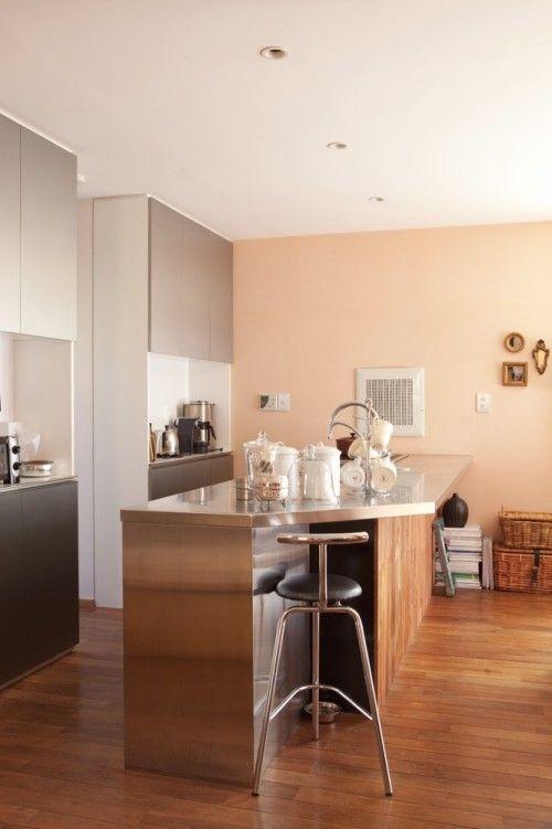 木の質感を生かしたカウンターにステンレストップのキッチン。<このミックス感がコリーさんの理想のイメージの源。ピーチオレンジの珪藻土の壁が、リゾートのくつろぎ感を醸しています。