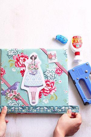 3.Tildaの布を貼ったパネルに 女の子のモチーフをボンドで貼り  好みのリボン・紙物を 木工用ボンドやテープのり、 タッカーでつけ、コラージュします。