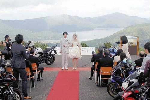 小田原市と箱根・伊豆方面を結ぶ有料道路「マツダターンパイク箱根」のスカイラウンジ駐車場で12日、バイク好きのカップルが結婚式を挙げ、ライダー仲間から祝福を