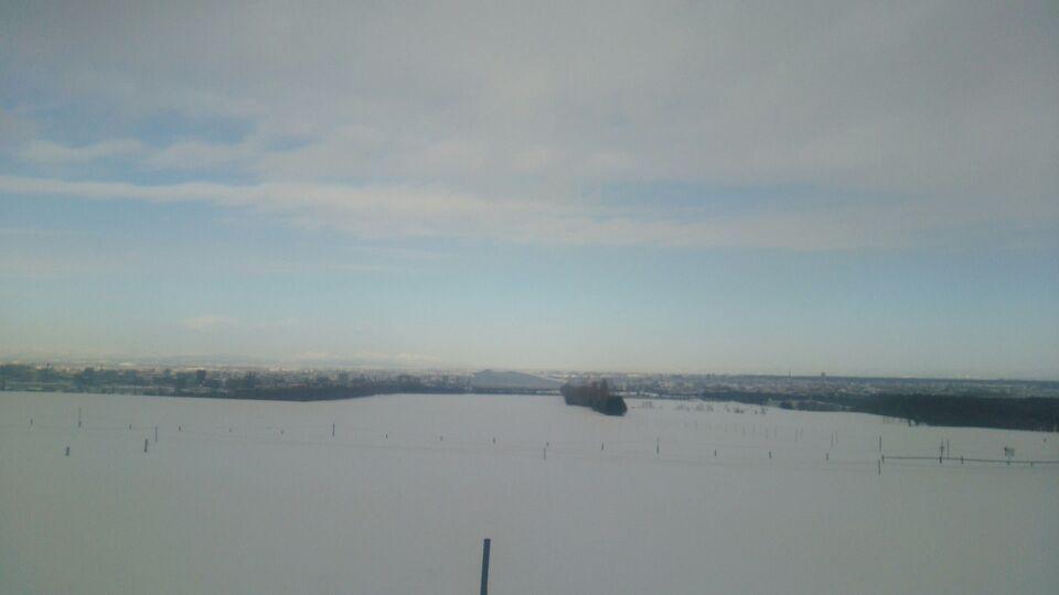 雪の平原と札幌の街並み