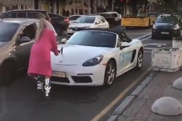 ウクライナのキエフ中心部で金髪女性がポルシェ  ロードスターを斧で破壊して逃走【動画】