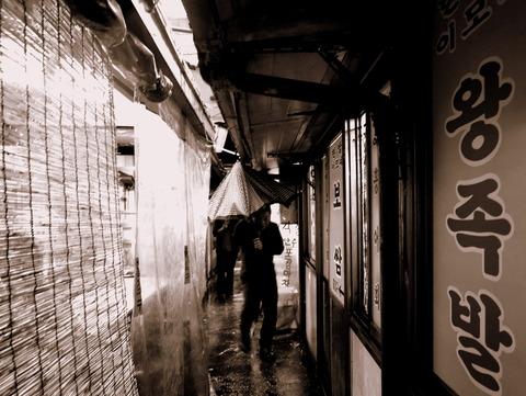 豚足の濡れ路地を忍者走りするスバシッコイ濡れ男