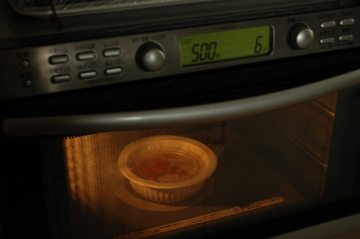 はがしたふたをのせ、容器を電子レンジで加熱する。