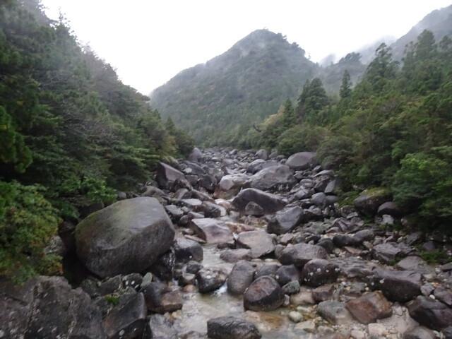 こんな石がごろごろした川にかかった橋を渡る