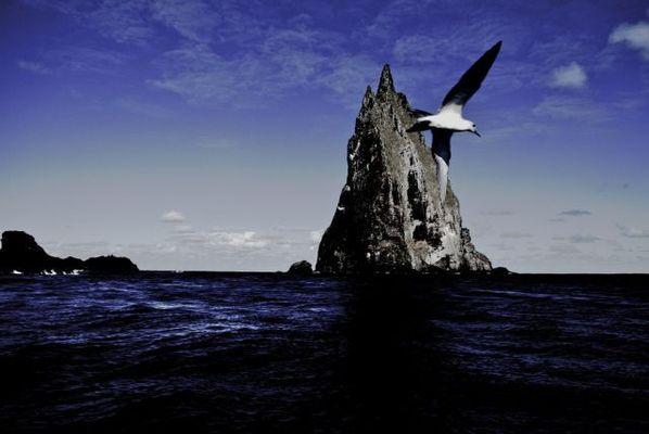 絶海に浮かぶ巨大な岩、空に突き...