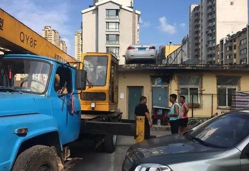 中国で違法駐車の車がクレーンで屋根の上に03