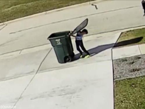 強風に吹き飛ばされかけながらゴミ箱を運ぶ少年01