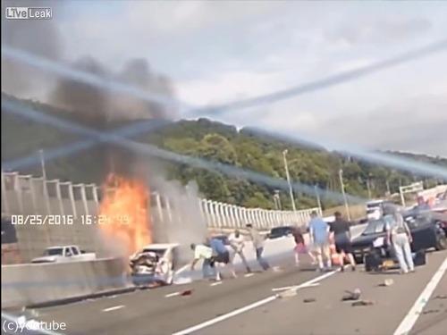 事故で燃える車から女性を救出する人々04