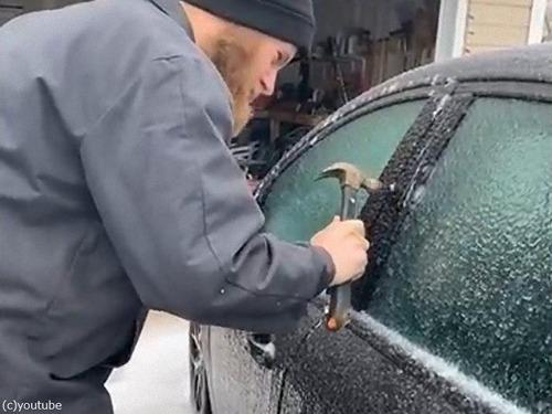 凍結した車のドアを金づちで開ける00