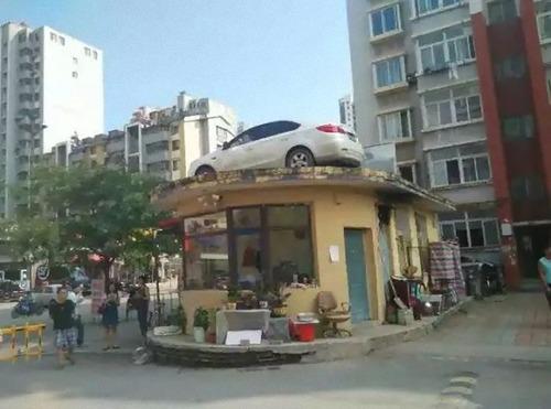 中国で違法駐車の車がクレーンで屋根の上に05