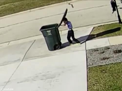 強風に吹き飛ばされかけながらゴミ箱を運ぶ少年03