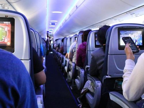 飛行機の中でテレビ画面を見ている