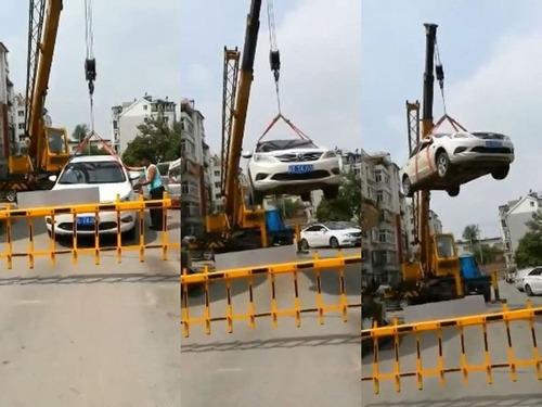 中国で違法駐車の車がクレーンで屋根の上に00