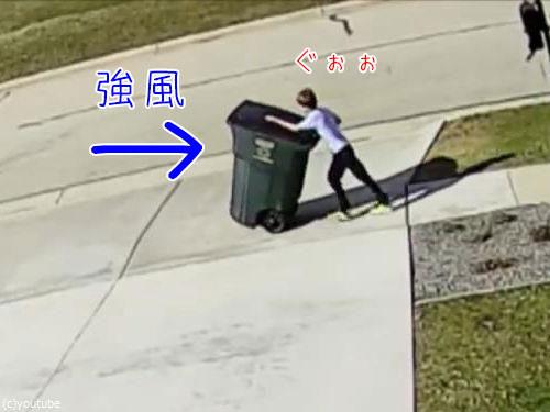 強風に吹き飛ばされかけながらゴミ箱を運ぶ少年00