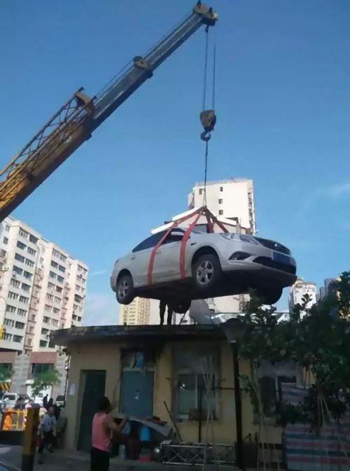 中国で違法駐車の車がクレーンで屋根の上に01