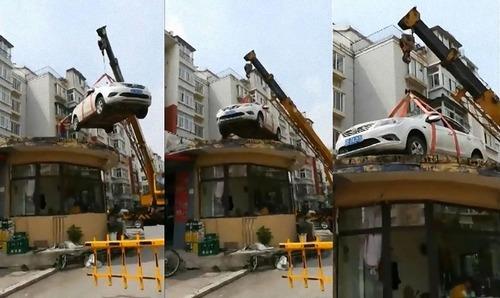 中国で違法駐車の車がクレーンで屋根の上に02